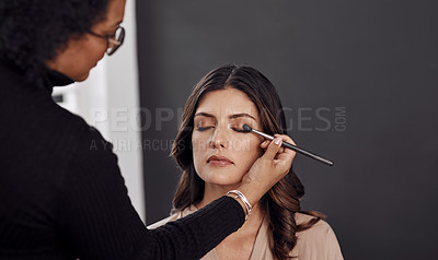 Buy stock photo Cropped shot of a woman having her makeup done by a makeup artist