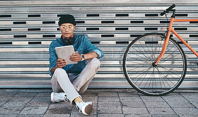 Buy stock photo Shot of a young man using a digital tablet while sitting outside with his bicycle