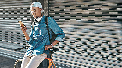 Buy stock photo Shot of a young man using his cellphone while standing outside with his bicycle