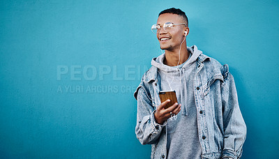Buy stock photo Cropped shot of a handsome young man using a cellphone against a blue background