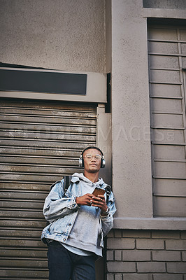 Buy stock photo Shot of a young man wearing headphone and using his cellphone while standing outside