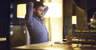 Buy stock photo Shot of a young businessman stretching while using a computer during late night at work