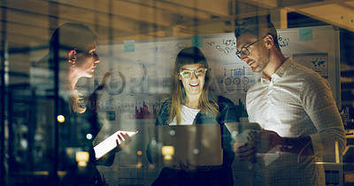 Buy stock photo Cropped shot of a group of business colleagues standing together and using technology to brainstorm in the office at night