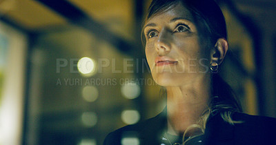 Buy stock photo Cropped shot of an attractive young businesswoman standing alone and looking contemplative in her office at night