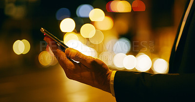 Buy stock photo Cropped shot of an unrecognizable businessman standing alone and texting on his cellphone while outdoors at night