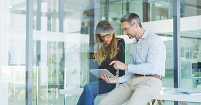 Buy stock photo Cropped shot of two business colleagues sitting together and using technology during a discussion in the office