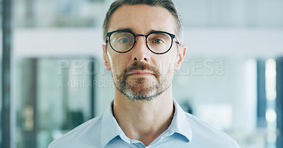 Buy stock photo Cropped shot of a handsome mature businessman wearing spectacles and standing alone in his office