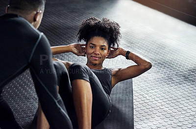 Buy stock photo Shot of a young man helping a woman do sit ups at the gym