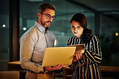Buy stock photo Shot of two businesspeople working together in an office at night
