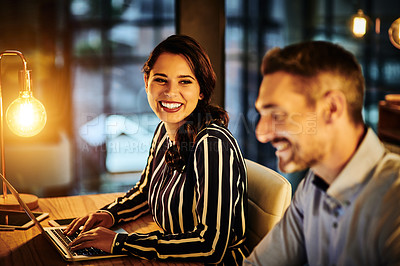 Buy stock photo Shot of two businesspeople working in an office at night