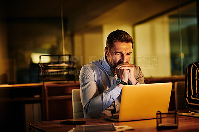 Buy stock photo Shot of a mature businessman looking anxious while working on a laptop in an office at night