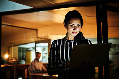 Buy stock photo Shot of a young businesswoman using a laptop in an office at night