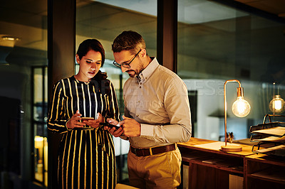 Buy stock photo Shot of two businesspeople using their cellphones in an office at night