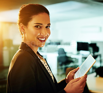 Buy stock photo Cropped shot of an attractive young businesswoman standing alone in her office and using a tablet at night