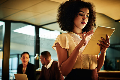 Buy stock photo Cropped shot of an attractive young businesswoman standing and using a tablet while her colleagues work behind her at night