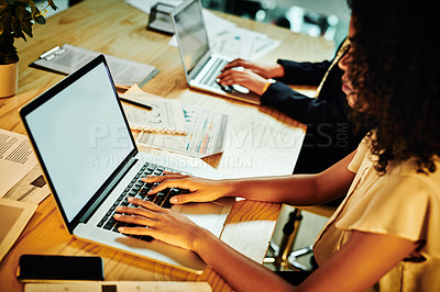 Buy stock photo Cropped shot of an attractive young businesswoman sitting with her colleague and using her laptop in the office at night