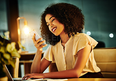 Buy stock photo Cropped shot of an attractive young businesswoman sitting alone in her office and texting on her cellphone late at night