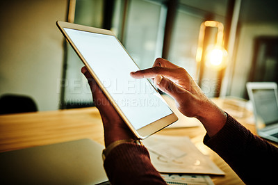 Buy stock photo Cropped shot of an unrecognizable businessman sitting alone in his office and using a tablet late at night