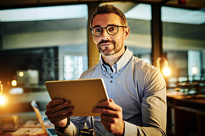 Buy stock photo Portrait of a mature businessman using a digital tablet in an office at night