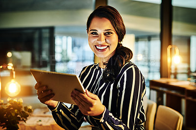 Buy stock photo Portrait of a young businesswoman using a digital tablet in an office at night