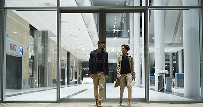 Buy stock photo Full length shot of two young businesspeople walking together after working a late shift in the office