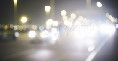 Buy stock photo Cropped shot of a busy highway that is brightly lit with street lamps and headlights during the night