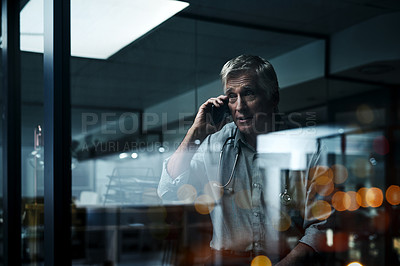 Buy stock photo Shot of a mature male doctor making a phone call in his office at night