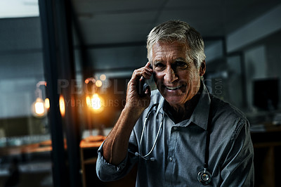 Buy stock photo Shot of a mature male doctor making a phone call while working late inside his office