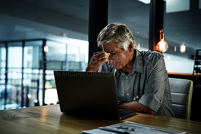 Buy stock photo Shot of a mature male doctor feeling stressed out while working on a laptop inside his office at night