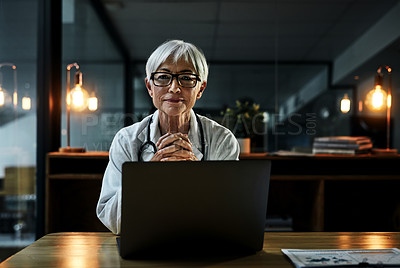 Buy stock photo Portrait of a mature female doctor working on a laptop inside her office at night