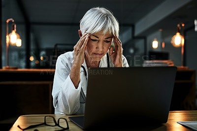 Buy stock photo Shot of a mature female doctor suffering from a headache while working on a laptop inside her office at night