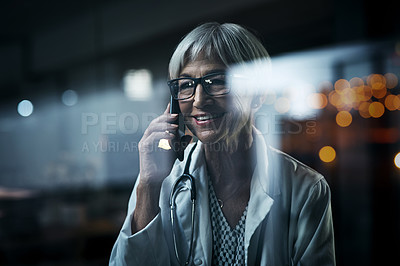 Buy stock photo Shot of a mature female doctor making a phone call inside her office at night