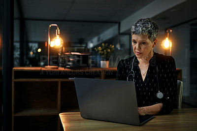 Buy stock photo Shot of a mature female doctor working on a laptop inside her office at night