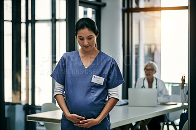 Buy stock photo Shot of a young and pregnant female nurse holding her stomach inside a hospital