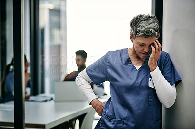 Buy stock photo Shot of a mature female nurse suffering from a serious headache while working inside a hospital