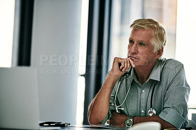 Buy stock photo Shot of a mature male doctor looking thoughtful while working on a laptop inside his office