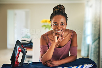 Buy stock photo Cropped shot of a young woman ironing clothes at home