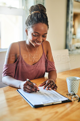 Buy stock photo Cropped shot of a young woman filling out paperwork at home