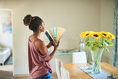 Buy stock photo Shot of a young woman fanning out color swatches at home