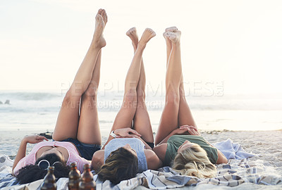 Buy stock photo Shot of three friends lying with their legs up at the beach