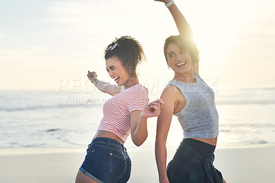 Buy stock photo Cropped shot of two female friends spending the day at the beach