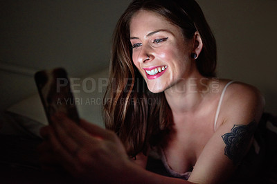 Buy stock photo Shot of an attractive young woman using her cellphone while relaxing in her bedroom at home