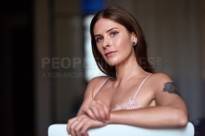 Buy stock photo Portrait of an attractive and confident young sitting on a chair and posing inside her apartment
