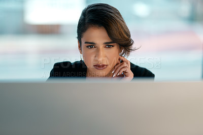 Buy stock photo Cropped shot of an attractive young businesswoman sitting alone and looking contemplative while working on her computer in the office