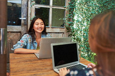 Buy stock photo Shot of a beautiful young woman using a laptop during a meet up with her friend at an outdoor cafe