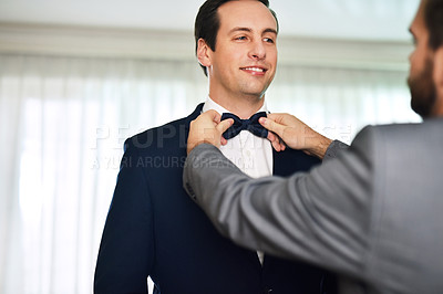 Buy stock photo Shot of an unrecognizable best man helping the bridegroom get dressed on his wedding day
