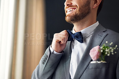 Buy stock photo Shot of an unrecognizable bridegroom adjusting his bowtie inside a changing room on his wedding day