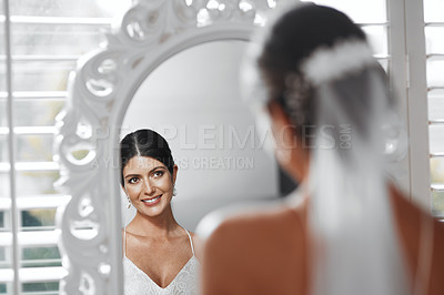Buy stock photo Rearview shot of an attractive young bride looking in the mirror while getting ready for her wedding ceremony