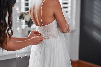 Buy stock photo Cropped shot of an unrecognizable bridesmaid helping the bride get ready for her wedding ceremony