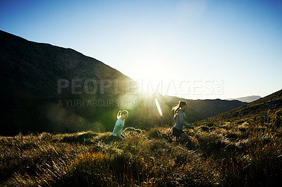 Buy stock photo Shot of two determined young women busy jogging together up on a mountain trail outside during the day